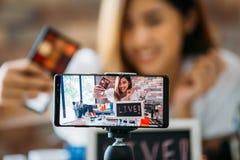 Χαμογελώντας ασιατική γυναίκα που παρουσιάζει σκιές ματιών στην επίδειξη του smartphone στοκ φωτογραφία με δικαίωμα ελεύθερης χρήσης