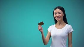 Χαμογελώντας ασιατική γυναίκα που παρουσιάζει χρυσή κάρτα στη κάμερα, απεριόριστη πίστωση, κατάθεση απόθεμα βίντεο