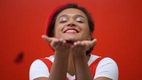 Χαμογελώντας γυναίκα που φυσά το καρδιά-διαμορφωμένο κομφετί από τα χέρια, εορτασμός βαλεντίνων απόθεμα βίντεο