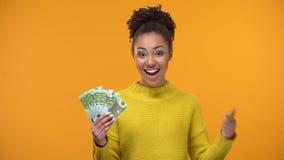 Χαμογελώντας κυρία αφροαμερικάνων που παρουσιάζει δέσμη των ευρώ στη κάμερα, υψηλός-που πληρώνεται την εργασία απόθεμα βίντεο