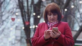 Χαμογελώντας μέση ενήλικη γυναίκα που χρησιμοποιεί τη χαλάρωση smartphone στο πάρκο Φω'τα στο υπόβαθρο απόθεμα βίντεο