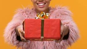 Χαμογελώντας μοντέρνο θηλυκό που παρουσιάζει κόκκινο κιβώτιο δώρων, γεγονός παρόν, χαιρετισμός γενεθλίων απόθεμα βίντεο