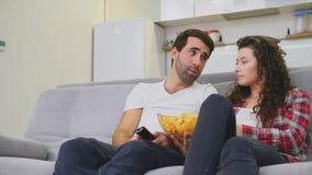 Χαμογελώντας συνεδρίαση συζύγων και ατόμων στον καναπέ Προσέξτε τη TV τρώγοντας τα τσιπ στο κρεβάτι Ντυμένος στα μαύρα εσώρουχα τ απόθεμα βίντεο
