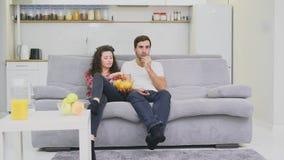 Χαμογελώντας συνεδρίαση συζύγων και ατόμων στον καναπέ Προσέξτε τη TV τρώγοντας τα τσιπ στο κρεβάτι Ντυμένος στα μαύρα εσώρουχα τ φιλμ μικρού μήκους