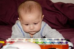 Χαριτωμένα 4 μηνών αγοράκι που έχουν το tummy χρόνο και που εξετάζουν το ζωηρόχρωμο xylophone στοκ εικόνες
