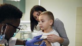 Χαριτωμένες νέες μητέρα και αυτή λίγος γιος στον παιδίατρο απόθεμα βίντεο