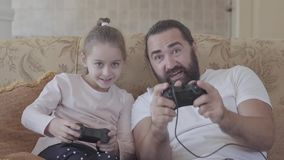 Χαριτωμένη μικρή κόρη με τον αστείο πατέρα της που παίζει τα τηλεοπτικά παιχνίδια στη TV με τις μεγάλες συγκινήσεις στο άνετο καθ απόθεμα βίντεο