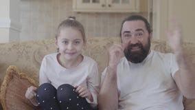 Χαριτωμένη μικρή κόρη με τον αστείο πατέρα της που προσέχει την ενδιαφέροντα ταινία ή τον αγώνα στη TV με τις μεγάλες συγκινήσεις απόθεμα βίντεο