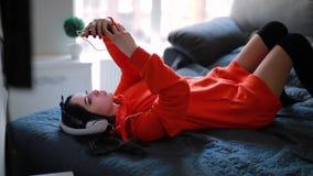 Χαριτωμένη μουσική ακούσματος κοριτσιών στον καναπέ ακουστικών στο σπίτι φιλμ μικρού μήκους