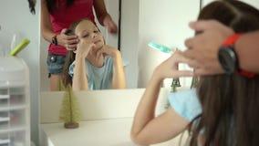 Χαριτωμένος κοριτσιών γύρω από το κοίταγμα που αντανακλά mom βουρτσίζοντας την τρίχα της φιλμ μικρού μήκους
