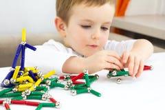 Χαριτωμένος λίγο παιχνίδι μαγνητών παιχνιδιού αγοριών παιδιών για την ανάπτυξη εγκεφάλου, τις λεπτές δεξιότητες μηχανών και την έ στοκ εικόνες
