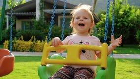 Χαριτωμένος χαμογελώντας λίγο κοριτσάκι που ταλαντεύεται σε μια ταλάντευση στη θερινή ημέρα κίνηση αργή απόθεμα βίντεο