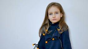 Χαριτωμένο κορίτσι με τη μακροχρόνια ξανθή τρίχα και τα μεγάλα μπλε μάτια που φορούν τη δέσμη των κίτρινων φω'των Χριστουγέννων σ απόθεμα βίντεο