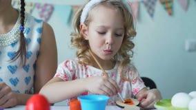 Χαριτωμένο κορίτσι που χρωματίζει το ξύλινο λαγουδάκι Πάσχας με τη βούρτσα απόθεμα βίντεο