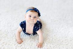Χαριτωμένο λατρευτό κοριτσάκι στα μπλε ενδύματα και headband λίγο παιδί που εξετάζει τη κάμερα και το σύρσιμο Εκμάθηση μωρών στοκ φωτογραφία