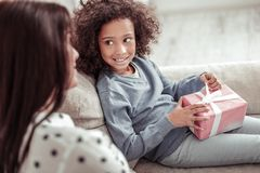 Χαριτωμένο μικρό κορίτσι που εξετάζει τη μητέρα της προσεκτικά στοκ φωτογραφία