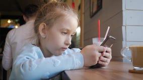 Χαριτωμένο μικρό κορίτσι που χρησιμοποιεί στο έξυπνο τηλέφωνο στον καφέ Ευτυχές παιδί που έχει τη διασκέδαση και που χαλαρώνει με φιλμ μικρού μήκους
