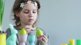 Χαριτωμένο μικρό κορίτσι που χρωματίζει τη βούρτσα αυγών Πάσχας whith στο χρώμα ασβέστη 2 όλα τα αυγά Πάσχας έννοιας νεοσσών κάδω απόθεμα βίντεο