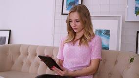 Χαριτωμένο ξανθό κορίτσι σε μια ρόδινη συνεδρίαση εμφάνισης μπλουζών ευρωπαϊκή στον καναπέ με μια ταμπλέτα κουβεντιάζοντας φίλοι απόθεμα βίντεο