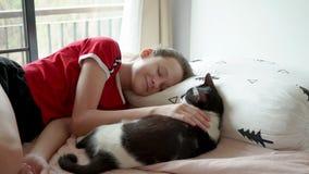 Χαριτωμένο παιχνίδι κοριτσιών εφήβων με τη γάτα και την πτώση της κοιμισμένες στο κρεβάτι απόθεμα βίντεο