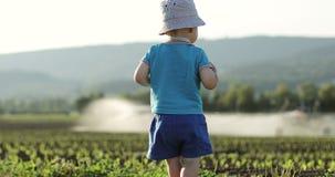 Χαριτωμένο παιχνίδι μωρών στο υπόβαθρο του εξοπλισμού για την άρδευση των γεωργικών τομέων απόθεμα βίντεο