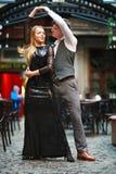 Χαρούμενα νέα ερωτευμένα χορεύοντας λατινικά ζευγών στην οδό βραδιού κοντά στον καφέ της παλαιάς πόλης στοκ εικόνες