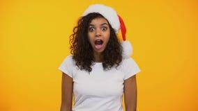 Χαρούμενη γυναίκα αναμιγνύω-φυλών στο καπέλο santa που λέει wow που εκπλήσσεται ευτυχώς με το δώρο απόθεμα βίντεο