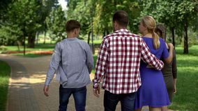 Χαρούμενη οικογένεια που περπατά στο κεντρικό πάρκο, Σαββατοκύριακο εξόδων μαζί, στήριξη στοκ εικόνα