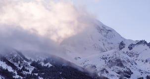 Χειμερινό βουνό Kazbek με το χιόνι, τρέξιμο σύννεφων, ηλιοβασίλεμα φιλμ μικρού μήκους