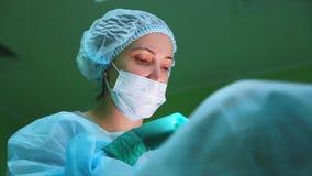 Χειρούργοι που φορούν τη προστατευτική ενδυμασία που εκτελεί τη χειρουργική επέμβαση που χρησιμοποιεί τον αποστειρωμένο εξοπλισμό φιλμ μικρού μήκους