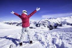 Χιονώδης θέα βουνού Νέα ευτυχής γυναίκα snowboarder που στέκεται στην κορυφή των όπλων αύξησης βουνών στον ουρανό Βόρειες Άλπεις, στοκ εικόνες