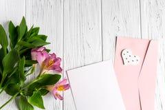 Χλεύη επάνω στο κενούς έγγραφο και το φάκελο στο ξύλινο άσπρο υπόβαθρο με τα φυσικά λουλούδια του ρόδινου χρώματος Κενό, πλαίσιο  στοκ εικόνες