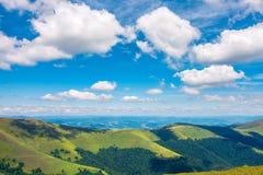 Χνουδωτά σύννεφα επάνω από την κορυφογραμμή βουνών στοκ φωτογραφία