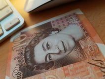 Χρήματα σημειώσεων λιρών αγγλίας εκτός από έναν υπολογιστή στοκ φωτογραφία