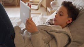 8χρονο αγόρι που βρίσκεται σε ένα κρεβάτι και που χρησιμοποιεί τον ψηφιακό υπολογιστή ταμπλετών απόθεμα βίντεο