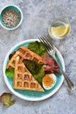 Χρόνος προγευμάτων Βάφλα με το prosciutto, τη σαλάτα και το αυγό για το πρόγευμα σε ένα συγκεκριμένο υπόβαθρο στοκ εικόνες