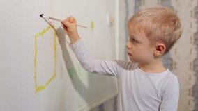 Χρώματα μικρών παιδιών με μια βούρτσα στον τοίχο στο σπίτι φιλμ μικρού μήκους