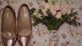 Χρυσές παπούτσια και ανθοδέσμη των γαμήλιων γυναικών απόθεμα βίντεο