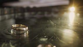 Χρυσή πτώση γαμήλιων δαχτυλιδιών σε έναν δίσκο με τη σαμπάνια φιλμ μικρού μήκους