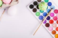 Χρωματισμένες χέρι αυγά Πάσχας, χρώματα και βούρτσες σε έναν άσπρο πίνακα Προετοιμασία για τις διακοπές στοκ φωτογραφία με δικαίωμα ελεύθερης χρήσης