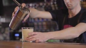 Χύνοντας κοκτέιλ αυγών μπάρμαν από το δονητή μετάλλων στο γυαλί με τον πάγο, που γυρίζει τον στον κύκλο Νεαρός άνδρας που κατασκε απόθεμα βίντεο