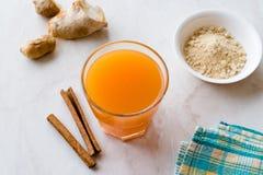 Υγιές ασιατικό ποτό Jamu με Turmeric και κανέλας το ραβδί, χυμός από πορτοκάλι στοκ εικόνα με δικαίωμα ελεύθερης χρήσης