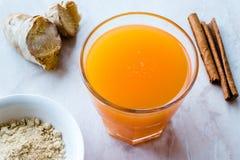 Υγιές ασιατικό ποτό Jamu με Turmeric και κανέλας το ραβδί, χυμός από πορτοκάλι στοκ εικόνα
