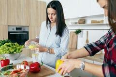 Υγιείς φίλες τρόπου ζωής που μαγειρεύουν τη φυτική εγχώρια κουζίνα θερινής σαλάτας στοκ εικόνες