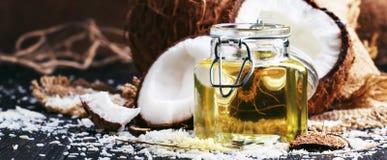 Υγρό πετρέλαιο καρύδων στο βάζο γυαλιού, σπασμένες καρύδες, σκοτεινός πίνακας, εκλεκτική εστίαση στοκ εικόνες