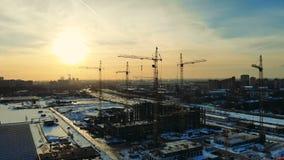 Υψηλοί γερανοί που λειτουργούν σε ένα εργοτάξιο οικοδομής σε μια πόλη απόθεμα βίντεο