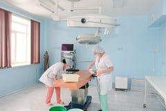 Υπάλληλοι νοσοκομείων στο νοσοκομείο Οι γιατροί προετοιμάζουν το λειτουργούντα πίνακα, χειρουργικός πίνακας Προετοιμασία για τη χ στοκ φωτογραφία