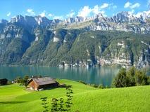 Υπέροχα δείτε με μια τυρκουάζ μπλε ελβετική λίμνη με τα χιονισμένα βουνά και τα ξύλινα σπίτια στοκ εικόνα