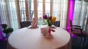 Υπέροχα διακοσμημένος πίνακας συμποσίου σε ένα ακριβό εστιατόριο Τουλίπες λουλουδιών ως όμορφη επιτραπέζια διακόσμηση απόθεμα βίντεο