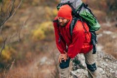 Υπαίθριος πυροβολισμός του νέου αρσενικού που στα βουνά που φορούν τα κόκκινα ενδύματα που ερευνούν τη νέα θέση Οδοιπορία ταξιδιω στοκ εικόνα